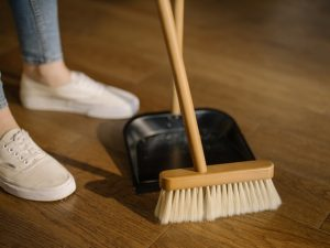 A person is cleaning the floor with a broom, since cleaning your new home is one of the first things you should do right after moving in.