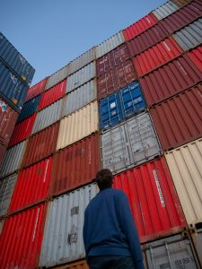 Man standing in front of shipping containers