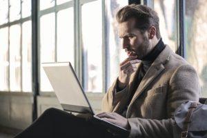 A man holding his chin facing a lap top