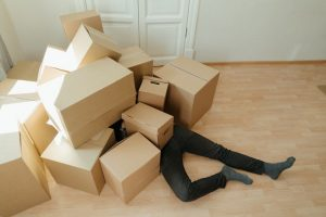 man under moving boxes